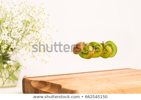 Sliced whole kiwi flying above a wooden chopping board Stock photo © deandrobot