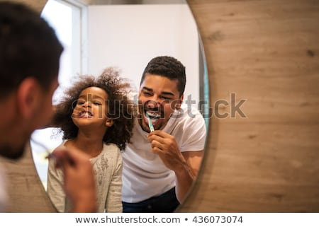Man in bathroom brushing teeth and smiling stock photo © monkey_business