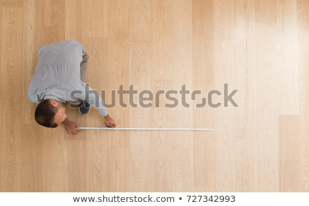 Сток-фото: Male Architect Measuring Wooden Plank With Tape Measure