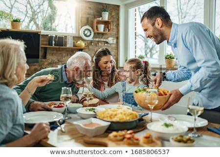 Family having meal on dining table Stock photo © colematt