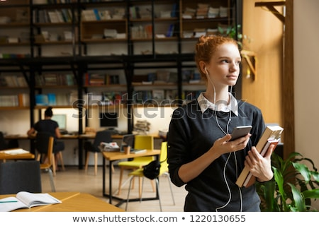 Redhead lady student posing indoors in library istening music with earphones. Stock photo © deandrobot