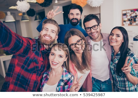friends or team photographing at office party Stock photo © dolgachov