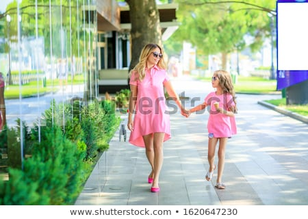 mother with little charming daughter are sitting in the city in sunlight mother feeds her daughter stock photo © elenabatkova