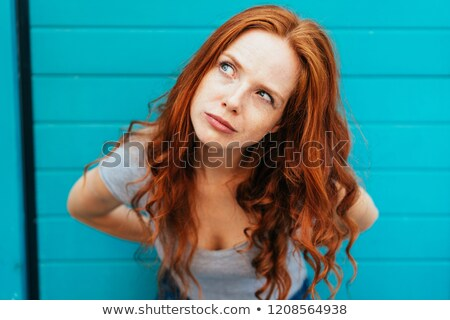 Thoughtful attractive redhead woman bending forwards and looking up to the side with a contemplative Stock photo © ElenaBatkova