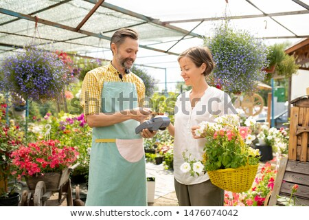 Male gardener or sales clerk in apron selling potted flowers to pretty woman Stock photo © pressmaster
