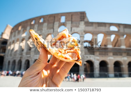 Hand Holding Italian Pizza Near Colosseum Stock photo © AndreyPopov