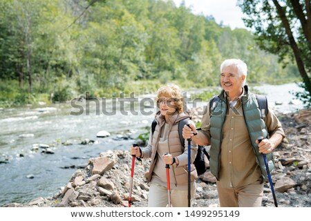Happy mature hikers with backpacks and trekking sticks walking along riverside Stock photo © pressmaster