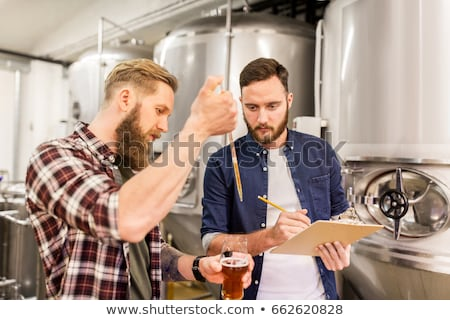 Stock photo: Men With Pipette Testing Craft Beer At Brewery