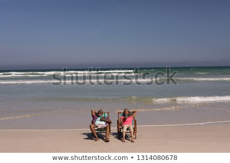 high angle view of senior couple relaxing on sun lounger and drinking cocktail on beach in the sunsh stock photo © wavebreak_media
