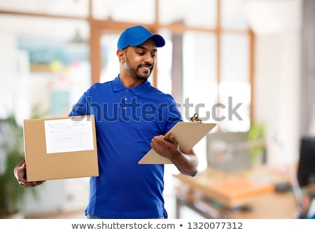 happy indian delivery man with clipboard in blue Stock photo © dolgachov
