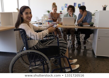 side view of pretty disabled mixed race female smiling at the camera in the office diverse business stock photo © wavebreak_media