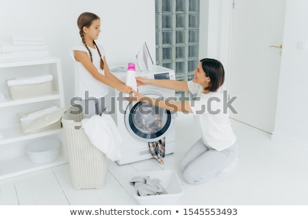 Lovely girl helps mum with washing, stands in basket, gives bottle of detergent or washing powder ,  Stock photo © vkstudio