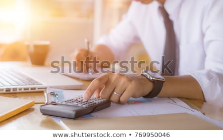 Hands working on accounting calculator calculating profit Stock photo © Elnur