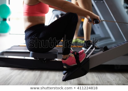 Woman using cycle machine in gym Stock photo © photography33