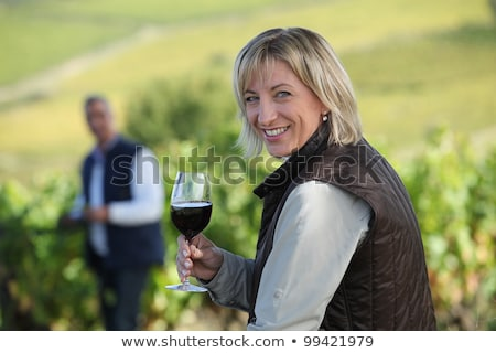 Stock photo: woman standing in vine rows with glass of wine