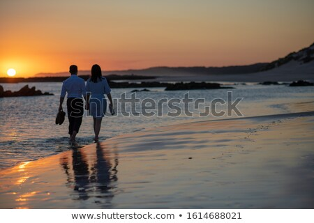 Couple taking romantic stroll along beach Stock photo © photography33