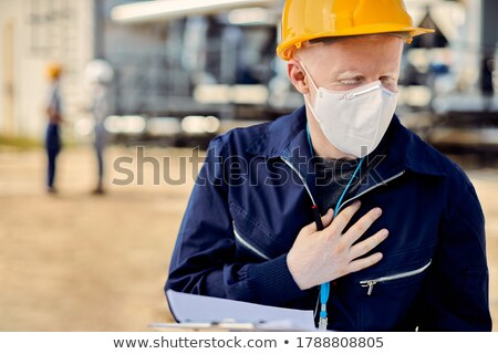 Construction worker holding his helmet to his chest Stock photo © photography33