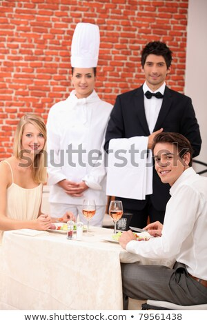 A couple being served by a waiter and a chef in a restaurant Stock photo © photography33