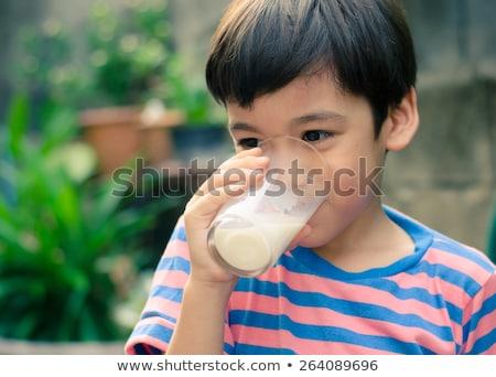 Happy kid drinking glass of milk Stock photo © get4net