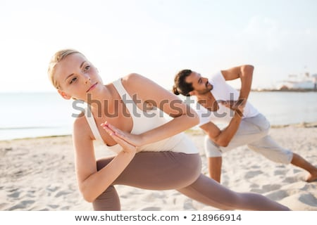 close up of couple making yoga exercises outdoors stock photo © dolgachov