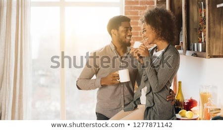 woman sitting and drinking coffee on the kitchen stock photo © deandrobot