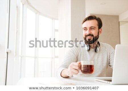 handsome bearded young man drinking tea and using laptop stock photo © deandrobot