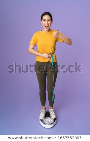 Stock photo: Woman standing on scales and holding tape measure around waist