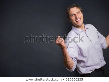 Man in lavender shirt holding up fist against navy chalkboard Stock photo © wavebreak_media