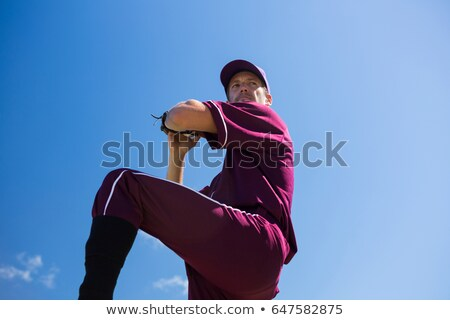 Low angle view of baseball pitcher throwing ball against blue sky Stock photo © wavebreak_media
