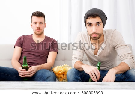 Happy man sitting at home indoors eating crisps. Stock photo © deandrobot