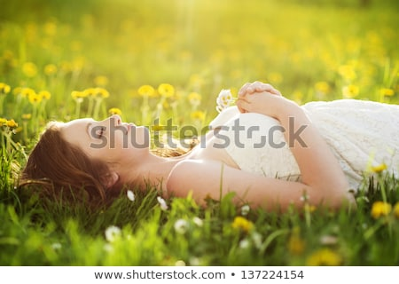 woman lying in grass with spring flowers stock photo © is2