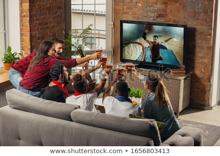 Stock photo: friends clinking beer and watching tv at home
