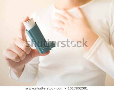 hand holds blue asthma inhaler for relief asthma stock photo © denismart