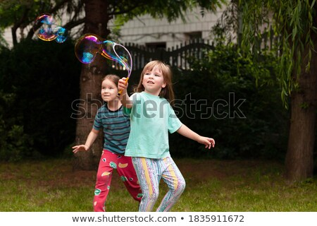 2 young girls chasing bubbles in park Stock photo © IS2