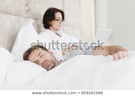 man asleep next to working girlfriend stock photo © is2
