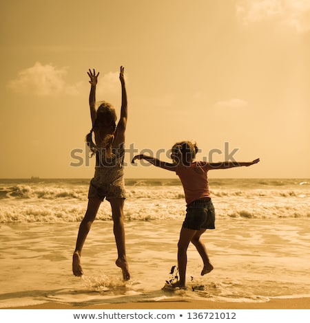 Girl playing in waves on beach Stock photo © IS2