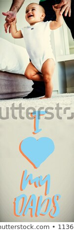 Close up of blue text with heart shape against father teaching baby to walk in bedroom Stock photo © wavebreak_media