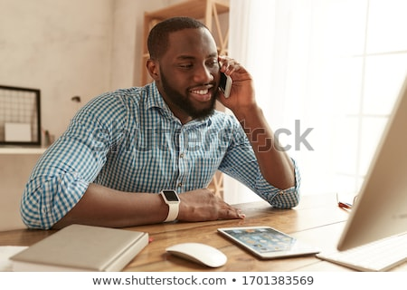 A young man is sitting in the office on the desk, talking on the phone and working with a computer. Stock photo © Traimak