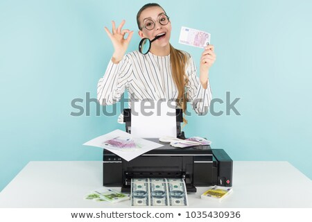 Attractive woman prints cash with magnifying glass Stock photo © Traimak