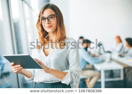 elegant businesswoman standing in office with digital tablet stock photo © boggy