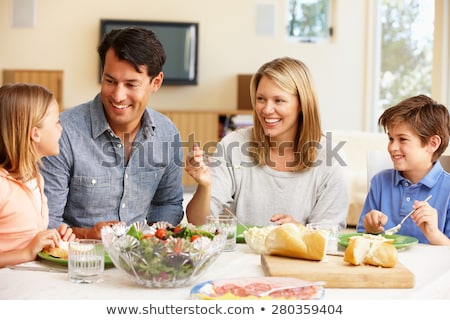 portrait of a happy family of four in the kitchen at home stock photo © lopolo