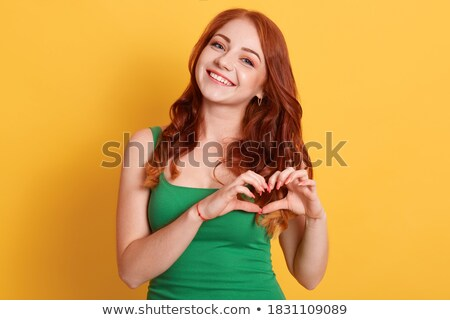 Young cute woman posing isolated over yellow background showing heart love gesture. Stock photo © deandrobot
