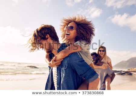 mixed race couple walking along beach with friends Stock photo © dolgachov