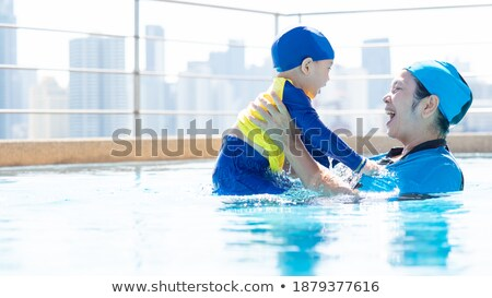Boy in outdoor swimming pool with city view in blue sky Stock photo © galitskaya