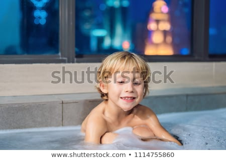 Happy little baby boy sitting in bath tub in the evening before going to sleep on the background of  Stock photo © galitskaya