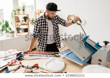 Young creative man printing or sticking decor on one of pet collar workpieces Stock photo © pressmaster