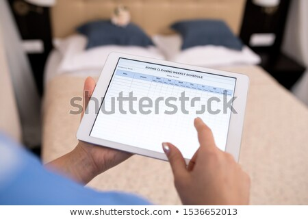 Hands of young chamber maid holding touchpad with electronic document Stock photo © pressmaster