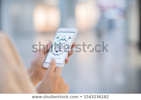 Hands of girl holding smartphone and going to enter online shop Stock photo © pressmaster