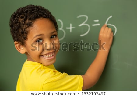 Rear view of happy smiling mixed-race schoolboy looking at camera while doing math on greenboard in  Stock photo © wavebreak_media