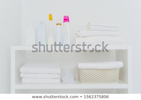 Laundry room with neatly folded towels, bottles of liquid washing or detergents. Everything in white Stock photo © vkstudio